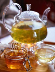 Stakleni čajnik i šalica ispunjeni čajem svijetlo zelene boje i staklena posuda s medom