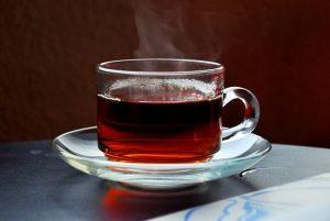 vreli čaj od rujevine u prozirnoj staklenoj šalici na staklenom tanjuriću
